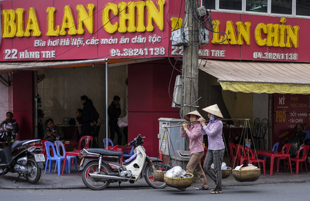 HANOI, VIETNAM - DECEMBER 11, 2014 : Vietnamese street market lady seller. They carrying a Òquang ganhÓ (two baskets slung from each end of a wooden or bamboo pole) filled up with food.