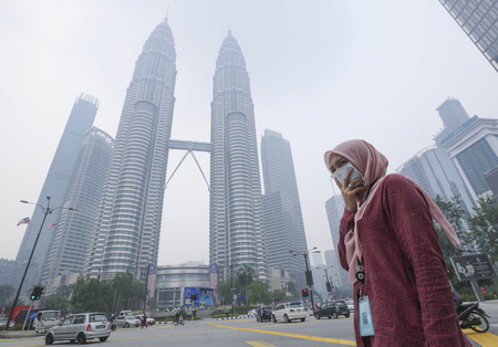 KUALA LUMPUR, MALAYSIA - SEPTEMBER 13, 2019 : A Women cover his nose and mouth with mask during haze because of unhealthy air quality as smoke from raging forest fires in Indonesia. Editöryel