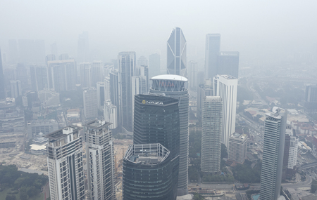 KUALA LUMPUR, MALAYSIA - SEPTEMBER 13, 2019 : Kuala Lumpur city buildings stand shrouded in haze because of unhealthy air quality as smoke from raging forest fires in Indonesia.