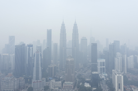 KUALA LUMPUR, MALAYSIA - SEPTEMBER 13, 2019 : The Petronas Twin Towers and other buildings stand shrouded in haze because of unhealthy air quality as smoke from raging forest fires in Indonesia. Editöryel