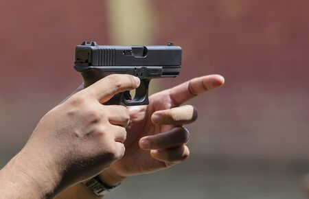 Close up view of hand holding a pistol  handgun taking aim for target.