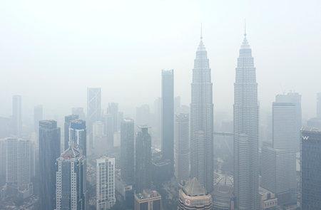 KUALA LUMPUR, MALAYSIA - 13. SEPTEMBER 2019: Die Petronas Twin Towers und andere Gebäude stehen wegen der ungesunden Luftqualität als Rauch von wütenden Waldbränden in Indonesien in Dunst gehüllt.