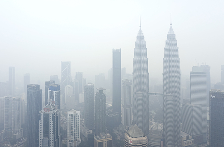KUALA LUMPUR, MALAYSIA - SEPTEMBER 13, 2019 : The Petronas Twin Towers and other buildings stand shrouded in haze because of unhealthy air quality as smoke from raging forest fires in Indonesia.
