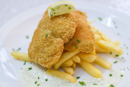 Fish and chips with french fries and tartar sauce. Fish and chips is a hot dish of English origin consisting of fried fish in batter served with chips.