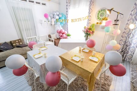 Birthday party decoration room with table setup and balloon.