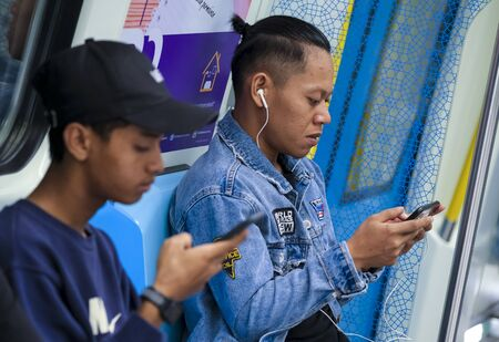 KUALA LUMPUR, MALAYSIA - FEBRUARY 22, 2020 : Passenger using mobile phone in Mass Rapid Transit (MRT) train to browsing web, listening music, playing games, texting and browsing social media.