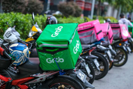 KUALA LUMPUR, MALAYSIA - MARCH 22, 2020 : Food delivery service rider for Foodpanda and GrabFood. Food delivery service through its mobile application.