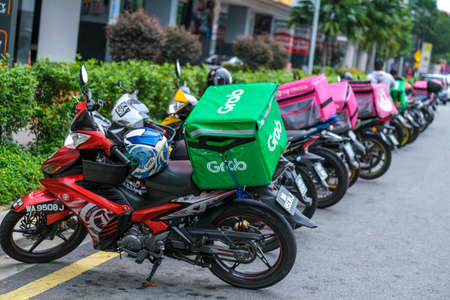 KUALA LUMPUR, MALAYSIA - MARCH 22, 2020 : Food delivery service rider for Foodpanda and GrabFood. Food delivery service through its mobile application. Editoriali