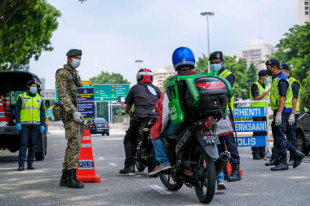 KUALA LUMPUR, MALAYSIA - MARCH 22, 2020 : Malaysia soldier and police inspect road users at a roadblock to enforce the order to stay at home, during the 'movement control order' COVID-19 outbreak.