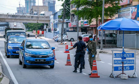 KUALA LUMPUR, MALAYSIA - APRIL 19, 2020 : Malaysia soldier and police inspect road users at a roadblock to enforce the order to stay at home, during the Movement Control Order COVID-19 outbreak. Editorial