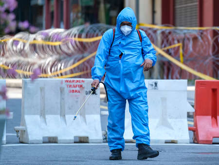 KUALA LUMPUR, MALAYSIA - APRIL 19, 2020: Police personnel from health department sanitizing lockdown area to prevent the spread of the Coronavirus disease 2019 (COVID-19) outbreak.