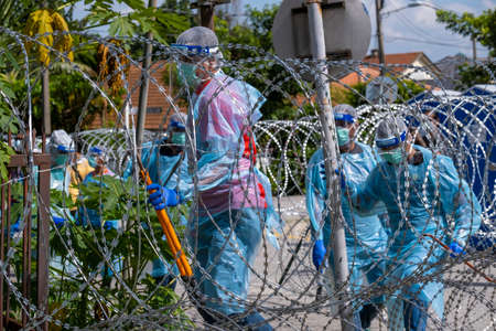 SELANGOR, MALAYSIA - MAY 12, 2020: A group of Police and local authorities wearing protective gear enter the locked down area in Petaling Jaya. Coronavirus disease 2019 (COVID-19) outbreak.