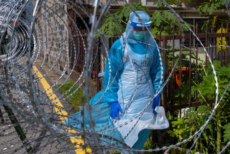 SELANGOR, MALAYSIA - MAY 12, 2020: A Police and local authorities wearing protective gear enter the locked down area in Petaling Jaya. Coronavirus disease 2019 (COVID-19) outbreak.