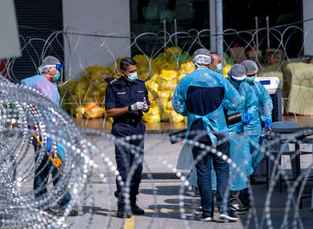 SELANGOR, MALAYSIA - MAY 12, 2020: A group of Police and local authorities wearing protective gear prepare to enter the locked down area in Petaling Jaya. Coronavirus disease 2019 (COVID-19) outbreak.