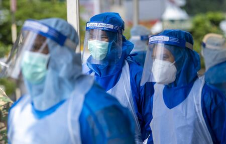 KUALA LUMPUR, MALAYSIA - MAY 15, 2020: Government health worker wearing a protective suit prepares to do the COVID-19 screening test to foreign workers. Coronavirus disease 2019 (COVID-19) outbreak. 版權商用圖片