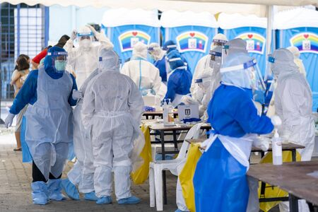KUALA LUMPUR, MALAYSIA - MAY 15, 2020: Government health worker wearing a protective suit prepares to do the COVID-19 screening test to foreign migrant workers. Coronavirus disease 2019 outbreak.