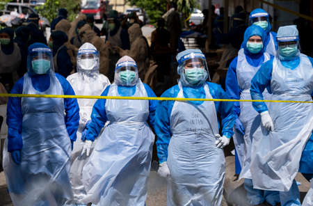 KUALA LUMPUR, MALAYSIA - MAY 15, 2020: Government health worker wearing a protective suit prepares to do the COVID-19 screening test to foreign workers. Coronavirus disease 2019 (COVID-19) outbreak.