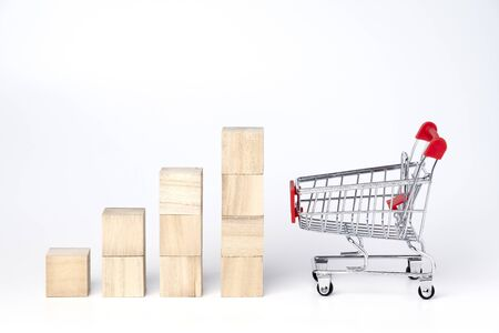 Graphs chart wooden cube block and trolley cart on a white background. Shopping, sale, finance and business concept.  Stock Photo