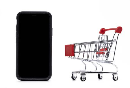 Empty trolley cart and mobile phone on a white background. Online Shopping, sale, finance and business concept.