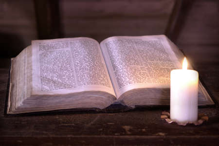 old histirical book with a candle on wood