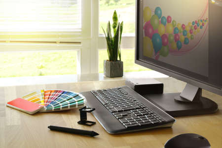 Desk of a graphic artist with monitor and color fan