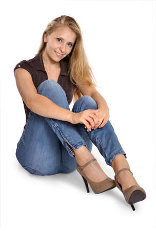 blonde woman sitting ground in jeans isolated 版權商用圖片