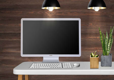 modern desk with monitor keyboard pens and plant