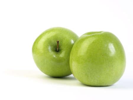 Dos manzanas verdes sobre fondo blanco  Foto de archivo
