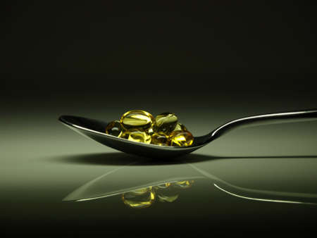 spoon yellow: Golden pills on a spoon
