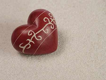 Red heart shaped stone on sand photo
