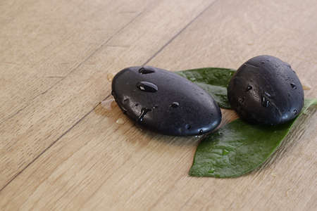 Wet Hot Stones with green leafs photo