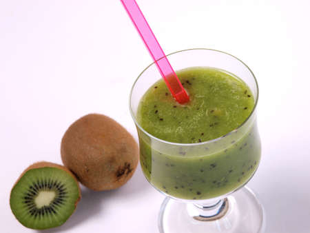 Glass of a kiwi smoothie with fresh fruits   photo