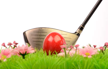 Red Easter egg on a green meadow with a golf  photo