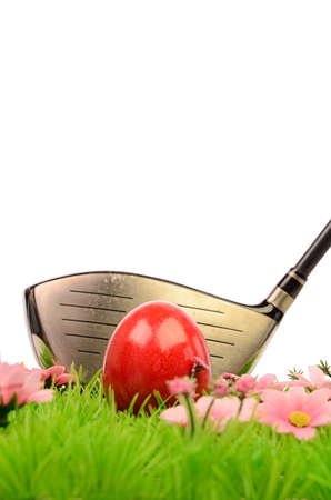 Red Easter egg on a green meadow with a golf club