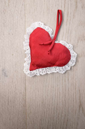 Red heart shape on a wooden background with space for text photo