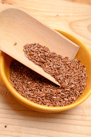 flaxseed: Flaxseed in a ceramic bowl on a wooden table