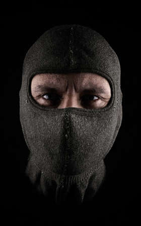 Masked man on a dark background photo