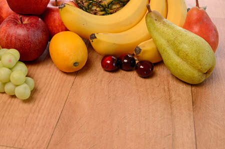 Fresh fruits on a wooden background photo