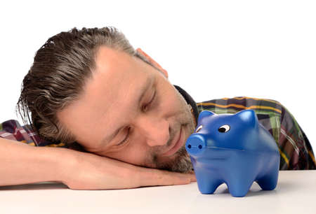 earned: Sleeping man with a blue piggy bank, financial concept