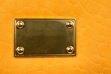 Gouden plaat met krassen op geel leer