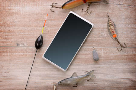 fishing gear: Fishing equipment with a cellphone on a wooden background Stock Photo