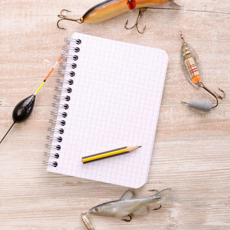Fishing equipment with a blank notebook on a wooden table photo