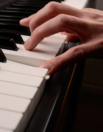 tocando piano: Detalle de la mano de tocar el piano Foto de archivo