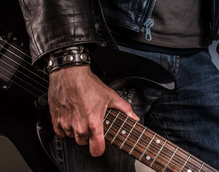 black leather: Rock star with an old scratched guitar