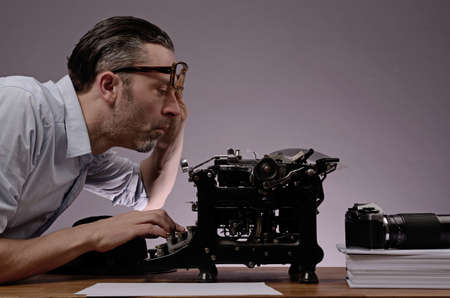 Editor with an old typewriter and retro camera on a wooden office table