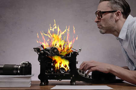 detective agency: Editor with an old typewriter working on a hot story Stock Photo