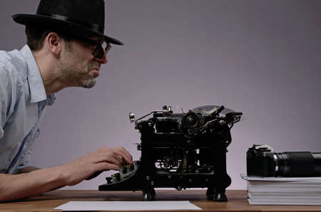 detective agency: Agent with an old type writer and a vintage camera in a dark office Stock Photo