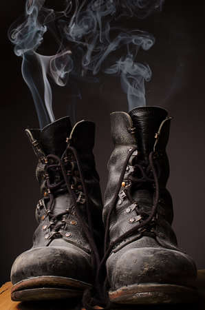 dirty feet: Old used working boots with smoke on a dark background Stock Photo