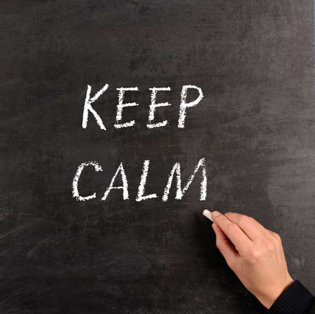 Hand writing with chalk KEEP CALM on a blackboard