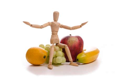 marioneta de madera: Marioneta de madera peque�a con frutas sobre un fondo blanco Foto de archivo